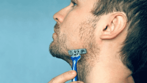 man using a disposable razor to shave his beard